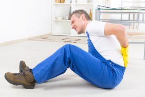 man injured on the job with lower back pain, in need of workers' compensation