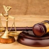 court mallet on a desk next to scales of justice