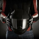 motorcycle rider holding a helmet