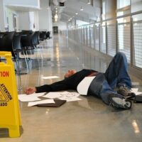 man on the floor next to a a wet floor sign